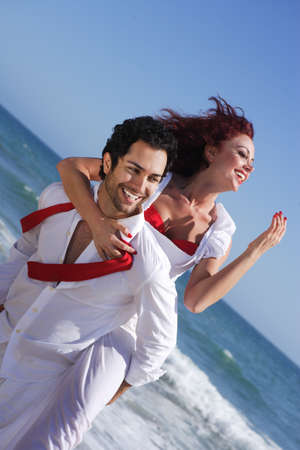 young couple enjoying on the beach, cheerful while on his back