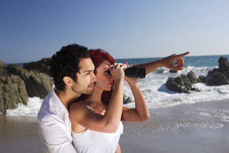 Young Couple at the beach looking through binoculars near rocks photo