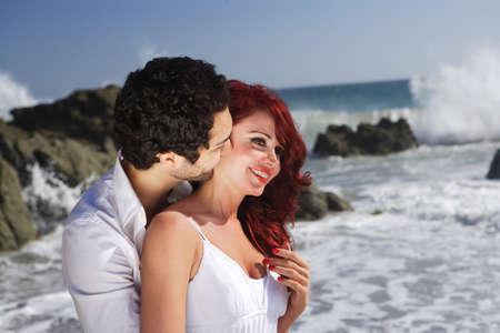 femme romantique: Jeune Couple � la plage montrant affection pr�s de roches Banque d'images