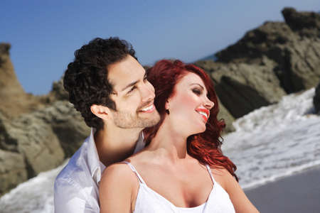Young Couple at the beach showing affection near rocks photo