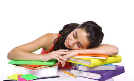 Teenage student sleeping on her books isolated on white