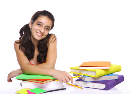young girl sitting in front of her books and smiling photo
