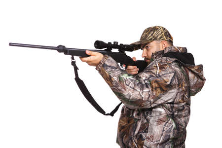 Hunter aiming a rifle while wearing camouflage clothing, isolated on white Stock Photo