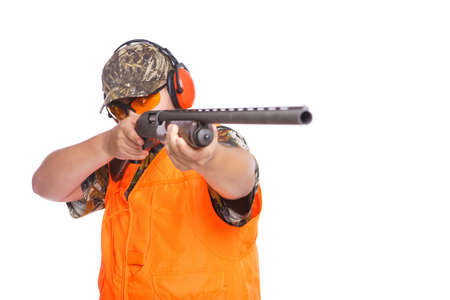 earphone: Hunter pointing shotgun at right side of the camera, isolated on white.  Stock Photo