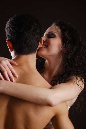 adult sex: young couple flirting with each other, while the woman is biting the mans ear
