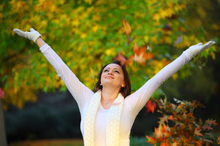 joyful woman standing infront of a tree with hands spread wide open looking at the sky Stock Photo