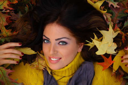 Young woman with autumn leaves laying down