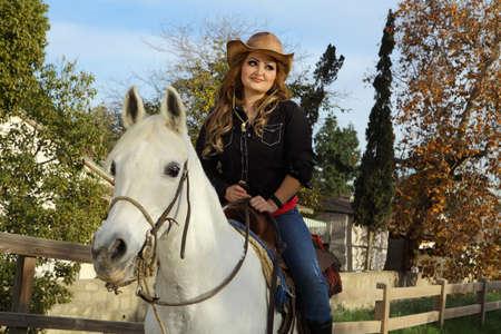 femme et cheval: Cowgirl assis sur son beau cheval blanc