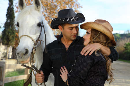 black cowgirl: Couple holding each other with a their white horse
