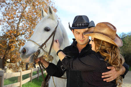 black cowgirl: Couple holding each other near a white horse