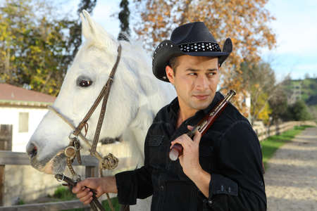 Cowboy with his beautiful white horse and gun photo