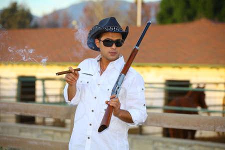 smoking cigar: Cowboy smoking a cigar with a rifle