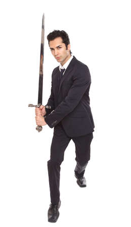Businessman with a sword in an attacking position photo