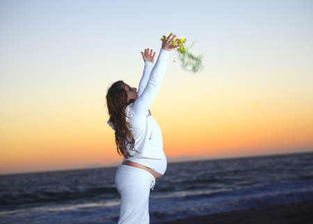 abdomen yellow jacket: Pregnant woman at the beach during sunset tossing flowers in the air Stock Photo
