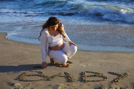 Pregnant woman at the beach writing  baby in the sand near the ocean