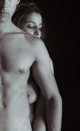 pareja desnuda: Pareja joven abrazados en el fondo negro