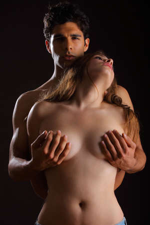 sex women: Young couple holding each other on black background