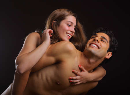 Young couple holding each other on black background photo