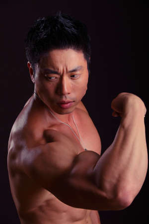 bicep: Side view of Asian Body Builder flexing bicep on black background