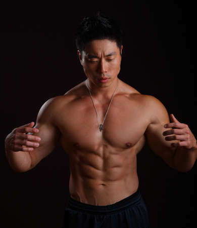 Asian body builder showing off his abs on black background