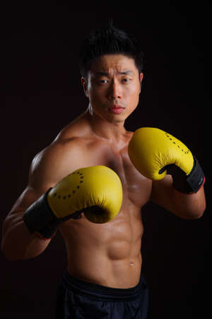 Asian boxer in his attacking stance with yellow gloves