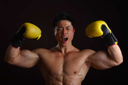Asian Man with yellow boxing gloves posing for the camera Stock Photo - 16940351