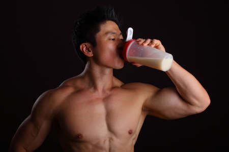 Asian Body Builder Drinking a Protein Shake on black background Stock Photo - 16940356