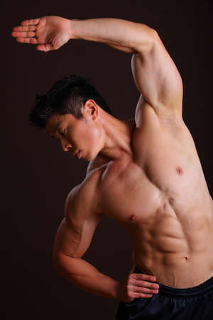 Muscle man stretching left arm and abs on black bacground photo