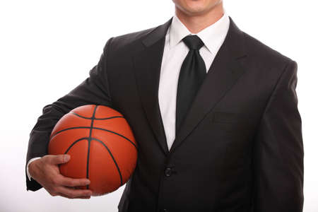 man in suite: Businessman holding a basketball without a head