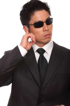 Asian Bodyguard listening to instructions wearing a black suite, glasses, and a tie.