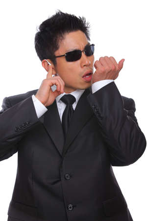 body guard: Asian Bodyguard talking in microphone listening to earpiece
