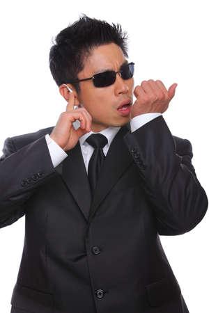 earpiece: Asian Bodyguard talking in microphone listening to earpiece