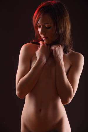 naked belly: A beautiful nude young woman against dramatic lighting with her arms folded over her breast.