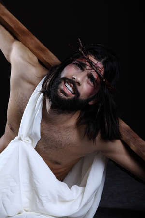strapped: Jesus looking up in hope with his hands strapped to the cross Stock Photo