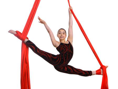 acrobacia: niña de gimnasia acrobática en el ejercicio de cuerda de tela roja, aislados en fondo blanco