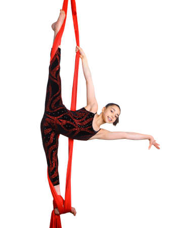acrobatic girl exercising on red fabric rope, isolated on white background photo