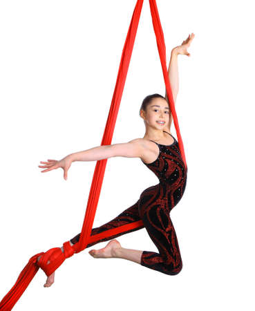 talent show: acrobatic gymnastic girl exercising on red fabric rope, isolated on white background Stock Photo