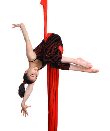 acrobatic gymnastic girl exercising on red fabric rope, isolated on white background photo