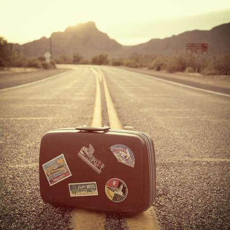 millennial: Vintage suitcase on road
