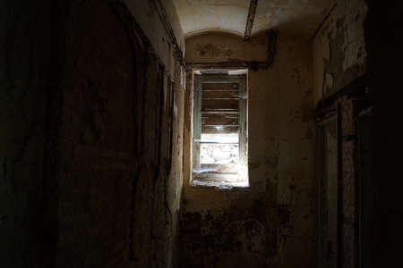 chiller: The interior of an old dark abandoned cell with a ruined window.