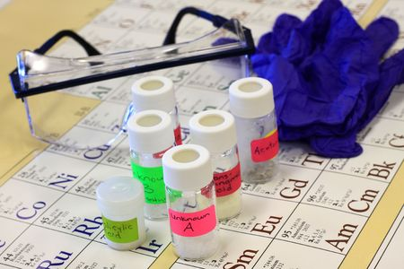 Different chemicals, safety glasses, and gloves on a periodic table. Banque d'images