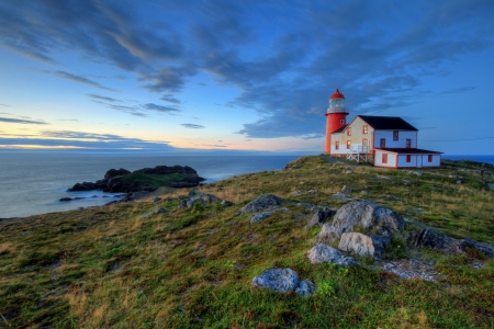 Newfoundland: Rocky coastline with lighthouse.  Stock Photo