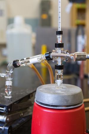 destilacion: Destilación de productos químicos con placa caliente, mezclador y termómetro.