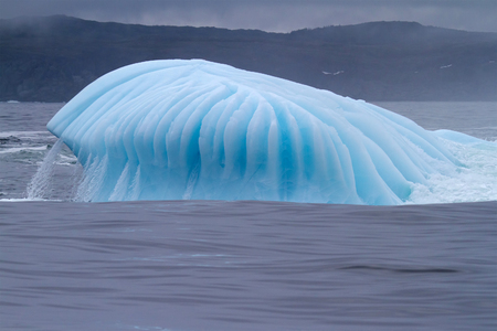 Iceberg with water flowing over.