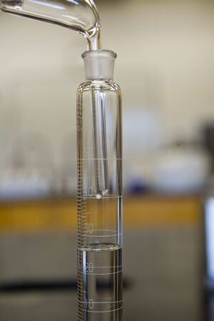 distillation: Collection of alcohol following distillation in achemistry laboratory. Stock Photo