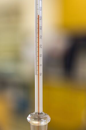 Close-up of an alcohol thermometer showing temperature in celsius. Фото со стока