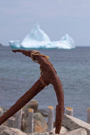 Anchor in foreground with iceberg in background.