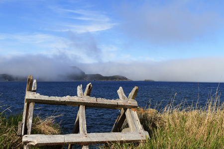 Old sawbuck abandoned along the foggy Newfoundland coastline Reklamní fotografie