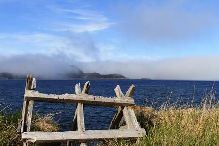 Old sawbuck abandoned along the foggy Newfoundland coastline Archivio Fotografico