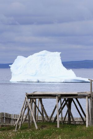 An iceberg gounded near an old fishing stage